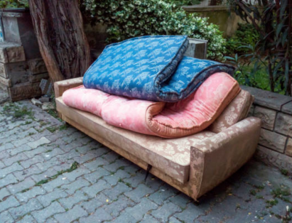 Couch And Mattresses Stacked On Sidewalk