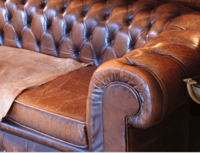 An old leather couch with cracked leather seats